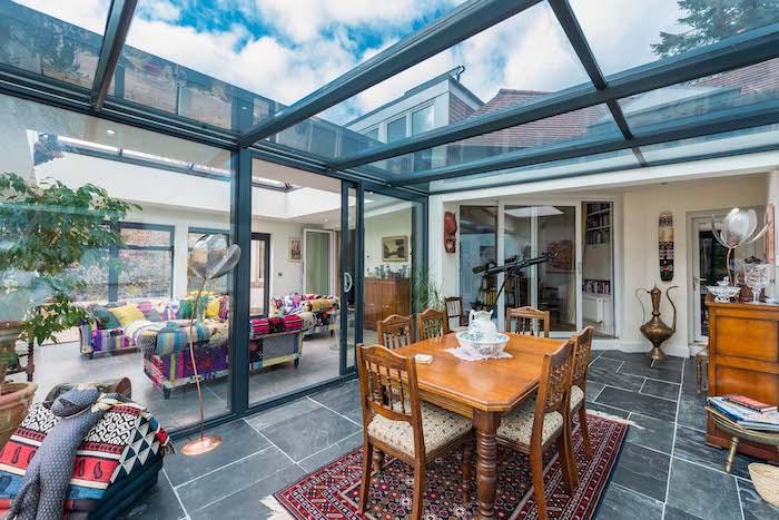 extension vitrée avec carrelage gris, coin salon avec fauteuils et canapé coloré et salle à manger bois sur tapis oriental