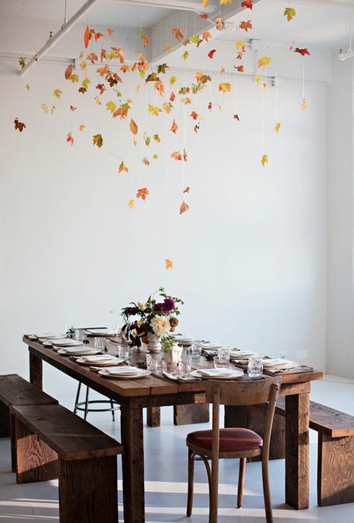 table de repas décorée, assiettes blanches sur table en bois foncé, centre de table vase, guirlande en feuilles d'automne