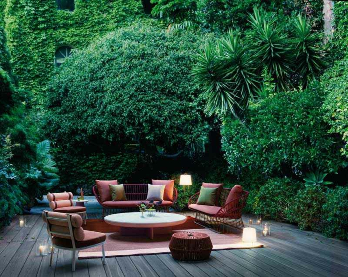 terrasse en bois, salon de jardin, table basse de salon, bougies allumées, grande haie d'arbustes vertes, palmiers