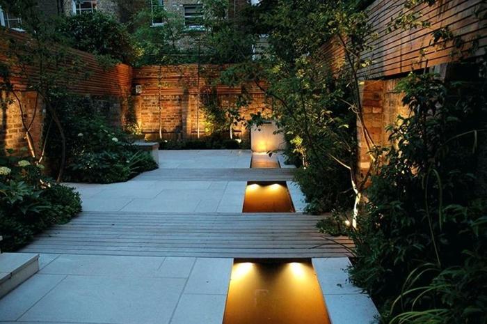 aménagement extérieur maison, murs en briques, parterres verts, éclairage romantique, arbres plantés, terrasse en dalles et bois
