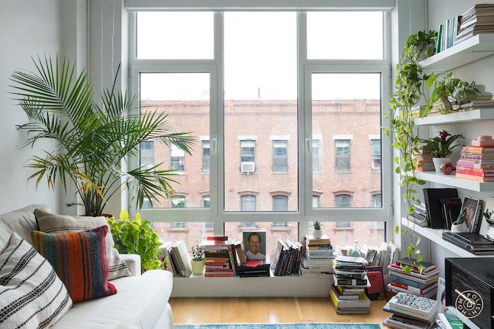 entassement de livres empilés, étagères bibliothèque blanche, parquet clair, palmier en pot, canapé blanc cassé, coussins décoratifs