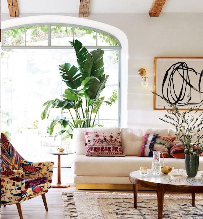 bananier en pot ans un salon boheme jungle urbain, murs blancs, grandes baies vitrées, tapis oriental, canapé blanc cassé, table basse ronde, poutres apparentes bois brut