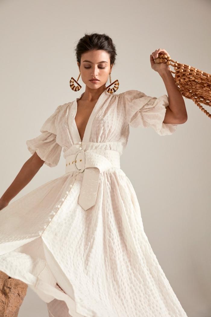 avec quoi assortir une robe blanche, tenue en robe fluide blanche avec accessoires boucles d'oreilles et sac à main marron