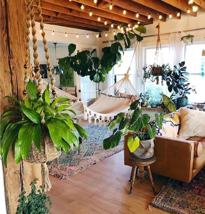 poutres apparentes sur le plafond, guirlande lumineuse, hamac d interieur, tapis oriental, canapé marron en cuir, deco boheme orientale