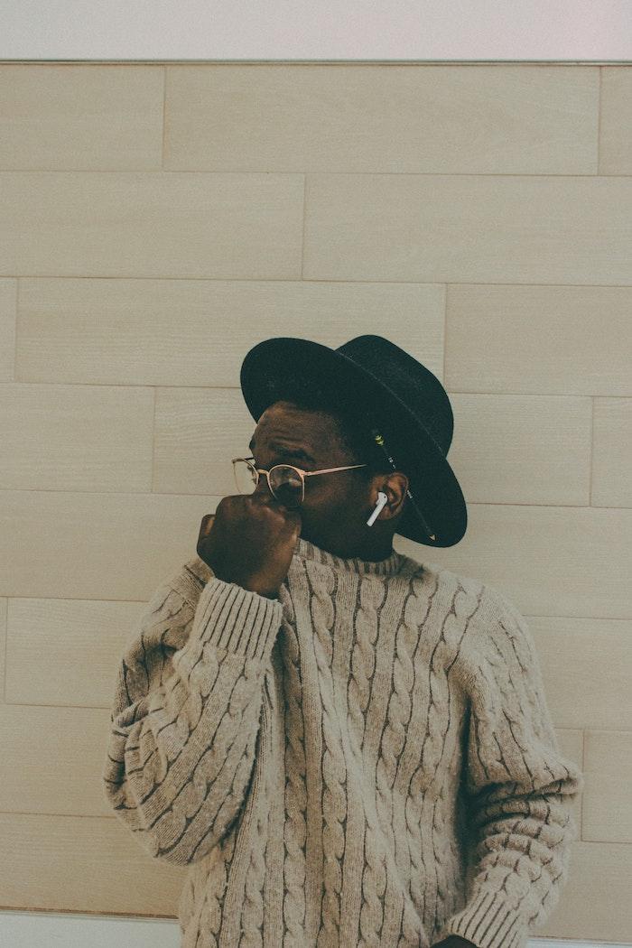 Homme en pull hipster style tenue avec chapeau rétro cool, écouteurs intra-auriculaire apple bluethoot, mec swag, le style des jeunes cool