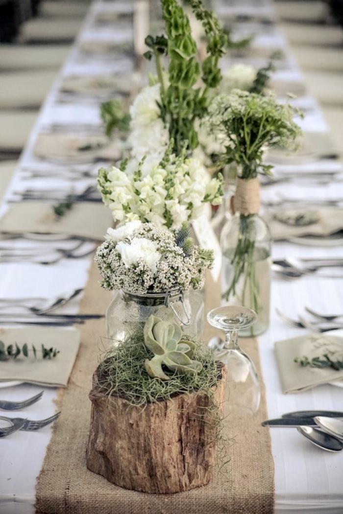 tronc de bois avec vases, petits arrangement blancs, nappes de table blanches, mousse verte