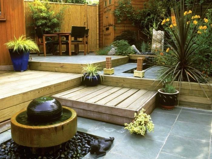 aménager son jardin de manière créative, grands pots de fleurs, parterres, fontaine moderne avec gravier gris, brise vue bois