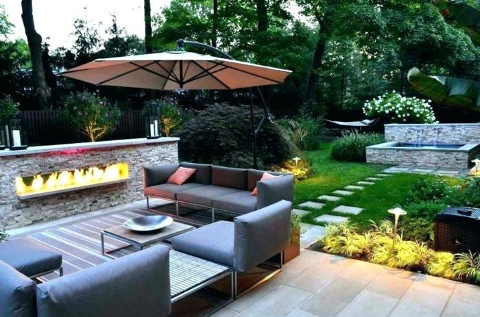 grand jardin paysager, sofas gris, foyer mural, muret pierre naturelle, parasol de jardin, allée en dalles au sein du gazon