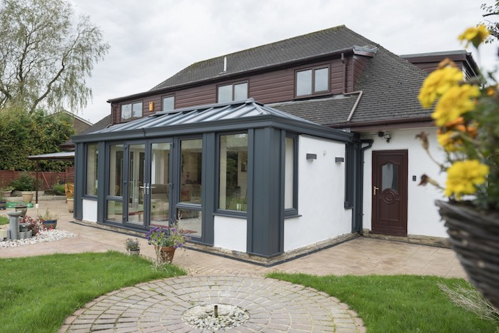 idee de agrandissement maison original avec de grosses portes vitrées et fenetres de toit, cour interieure maison avez gazin et dallage