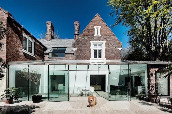 extension vitrée avec coin cuisine ouverte sur salle à manger blanche scandinave, terrasse en bois et maison de briques