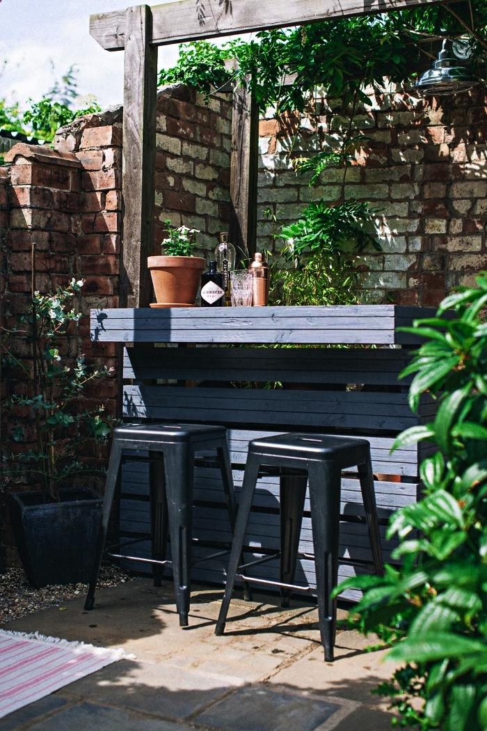 idée aménagement jardin et patio, fabriquer un bar de jardin avec des palettes récupérées, bar à cocktails en bois gris avec tabourets de bar de style industriel