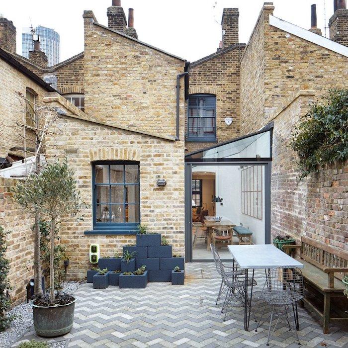 agrandissement entre deux murs pour amenager une salle à manger en longueur, maison de briques ouverte sur cour en dalles de beton et petite salle à manger en plein air