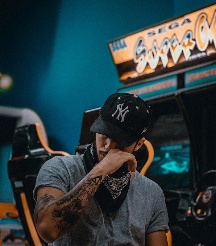 Homme moderne dans une salle de jeux vintage, cool photo d'homme tatouage swag sur l'avant bras