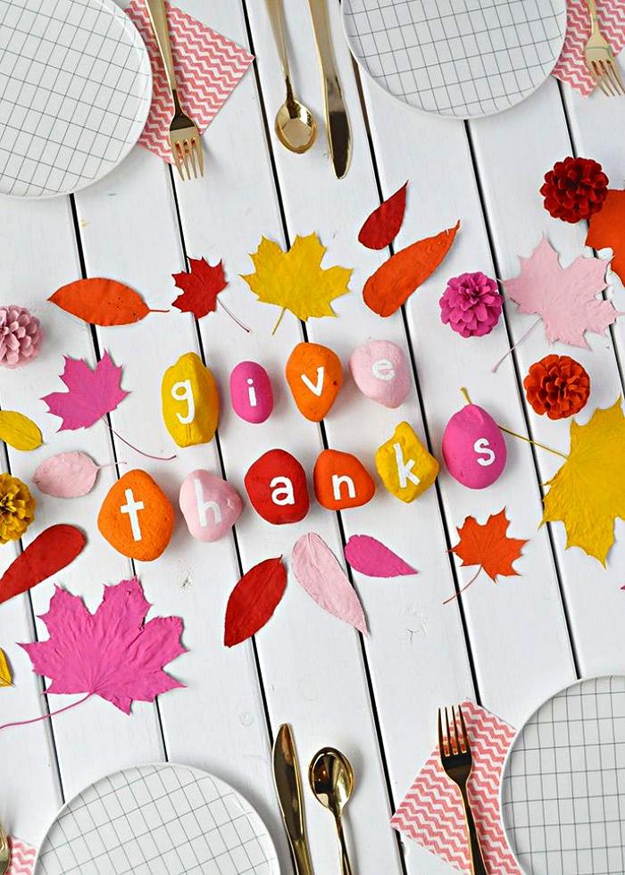 idée deco galet couleur vitaminée, déco de table avec galets à message personnalisé et des feuilles d'automne peints en teintes naturelles