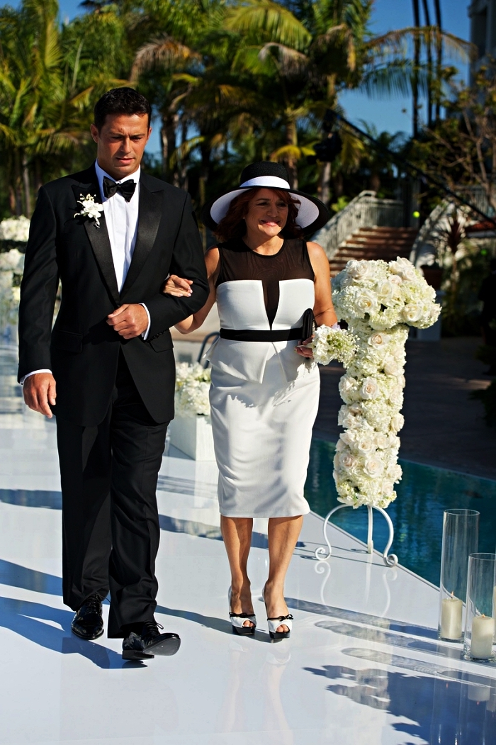 robe péplum en blanc et noir avec empiècement en tulle noire accompagnée d'un chapeau de mariage assorti, tenue mariage femme 50 ans pour la mère de la mariée