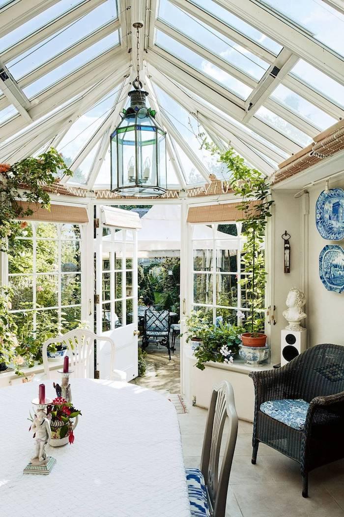 idee veranda victorienne blanche avec de petites fenetres de toit, coin salle à manger et chaise de rotin