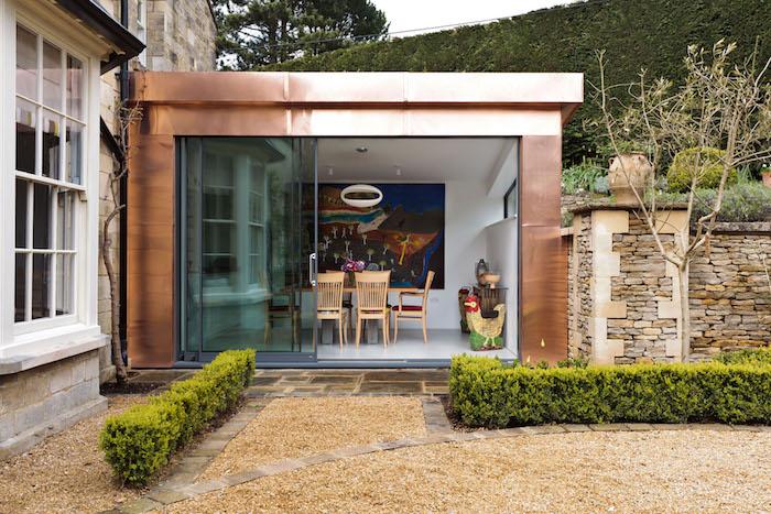 agrandissement original effet laiton pour accueillir une salle à manger en bois avec tableau peinture pour deco murale, ouverture sur cour d une maison