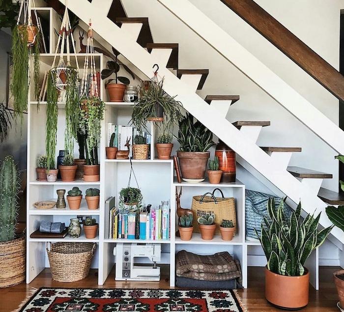 amenagement sous escalier, étagères blanches à plusieurs livres, objets deco et plantes en pots, pots suspendus et sansevière sur sol, plante d intérieur originale