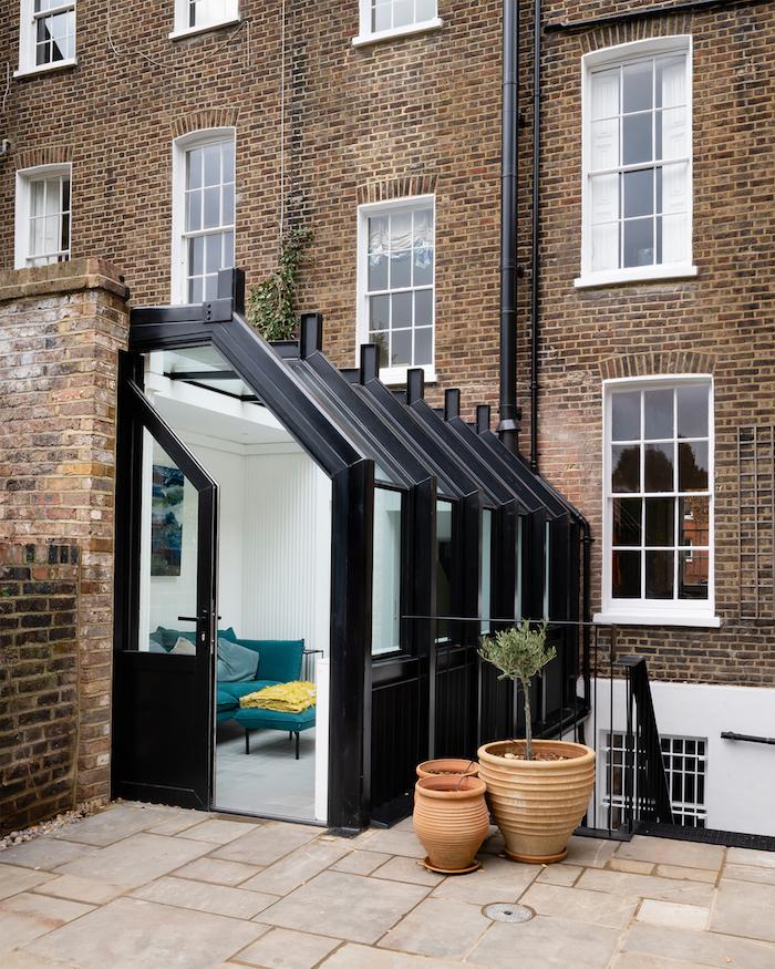 agrandir sa maison avec une petite extension contemporaine style industriel pour accueillir un coin repos avec table et canapé bleu canard