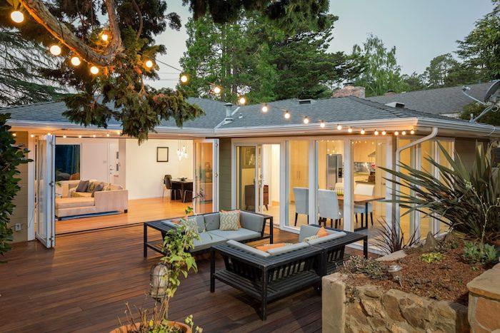 idee d extension maison enorme, batiment attenant ouvert sur une terrasse de bois avec deux bancs de bois, deco guirlande lumineuse exterieure