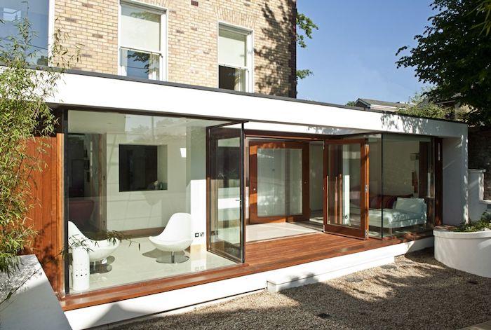 idee de design minimaliste d extenion vitrée avec lit et coin repos en fauteuils blancs, extension maison toit plat