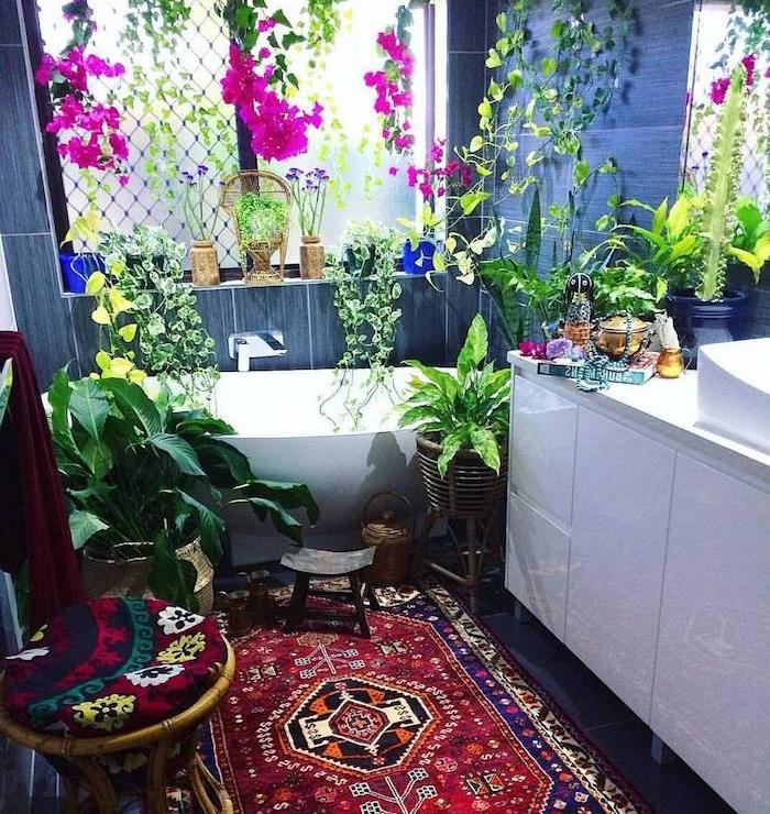 idee plante salle de bain, plusieurs espèces végétaux vertes et fuchsia, tapis oriental, meuble salle de bain blanc, carrelage gris salle de bain