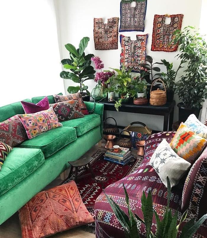 idee salon deco tropicale avec canapé vert et canapé bordeaux décorés de coussins orientaux, murs à panneaux décoratifs à l orientale, plantes vertes par sol et sur table de service noire