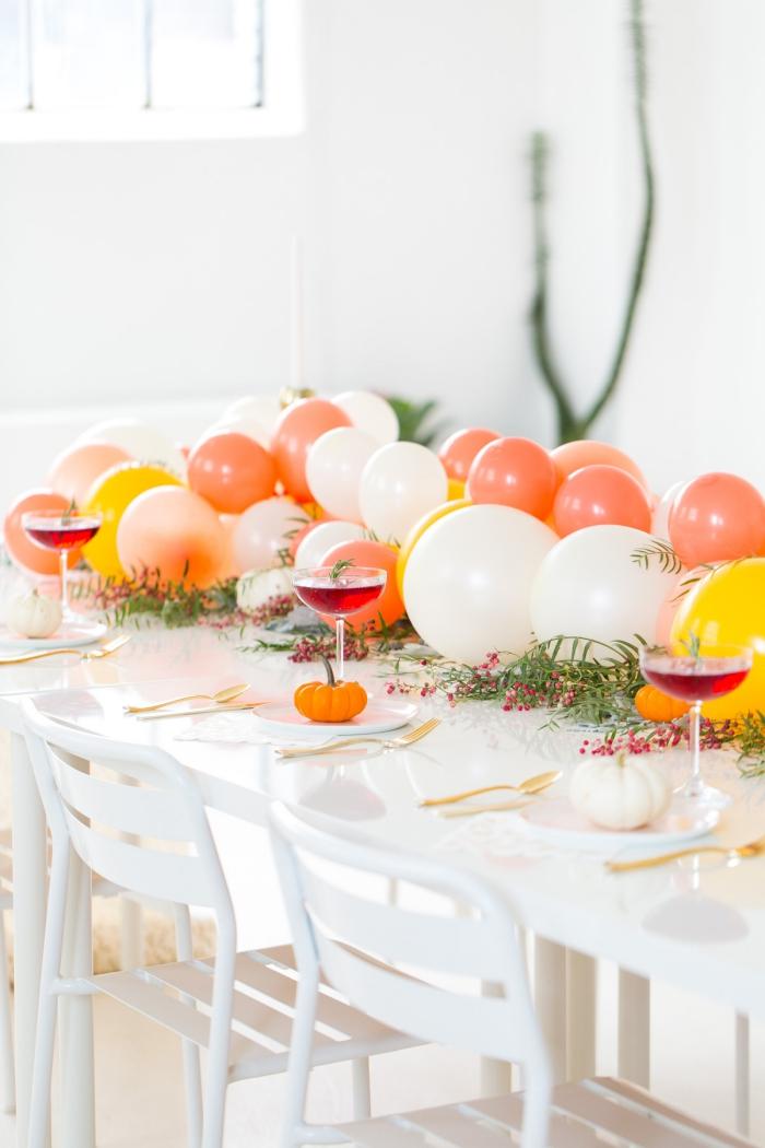 idee deco table avec ballons, verres à vin, mini citrouilles, guirlande de ballons comme chemin de table, ustensiles dorés