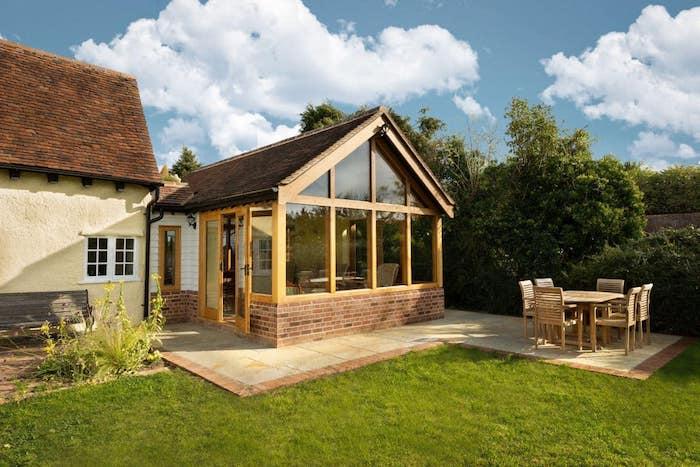 extension bois sur une terrasse en carrelage beige avec une petite salle à manger en plein air à coté, gazon vert