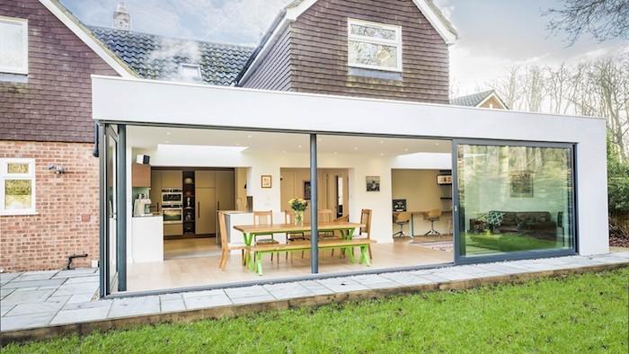 comment agrandir sa maison avec une extension moderne vitrée pour accueillir un studio 20 m2 avec cuisine ouverte sur salle à manger et salon avec canapé en cuir marron