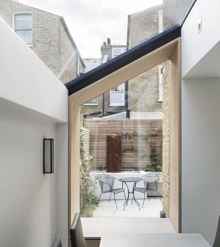 idee d extension entre deux murs avec coin repas constitué de table ronde et chaises metalliques entre vitres