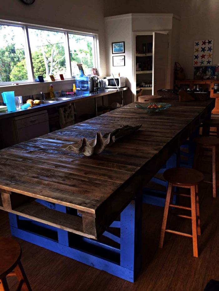 une grande table en bois rustique avec plateau en palettes, ilot central palette