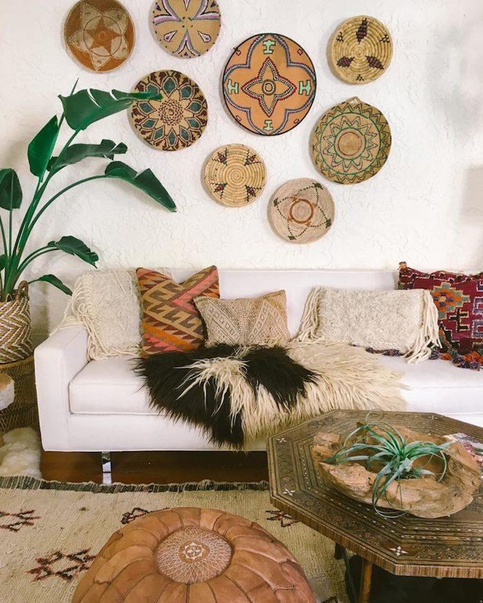 Deco salon style ethnique, décoration murale sur mur blanc, canapé blanc, plante verte, table bois hexagon