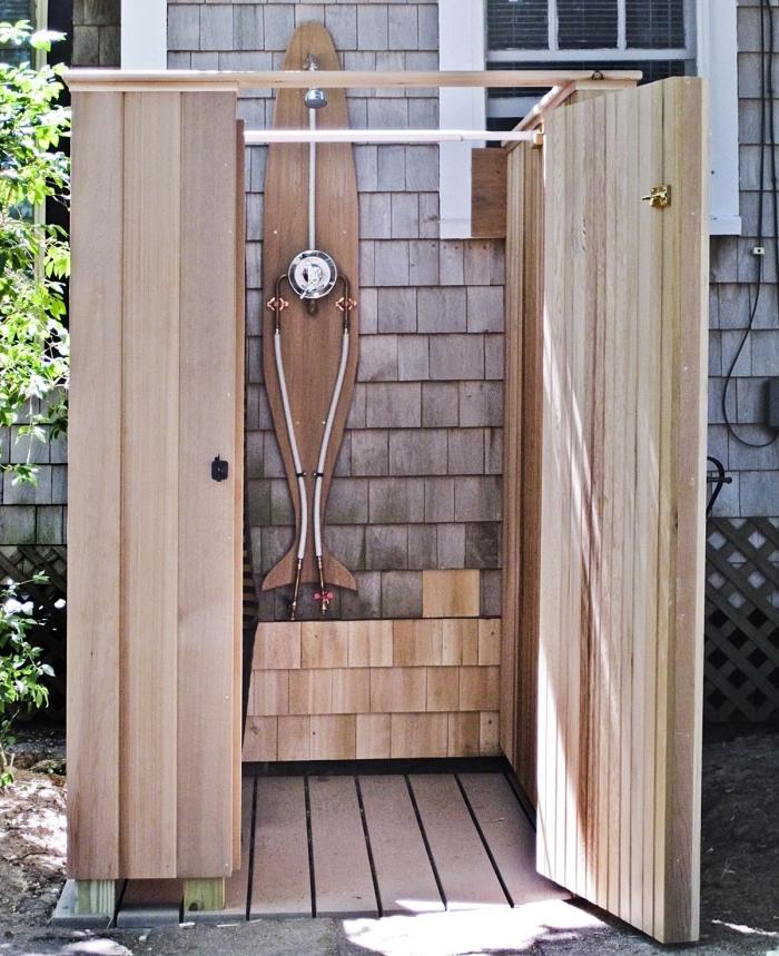 modèle de petite salle de bain dans le jardin avec receveur de douche en bois et pommeau de douche en inox