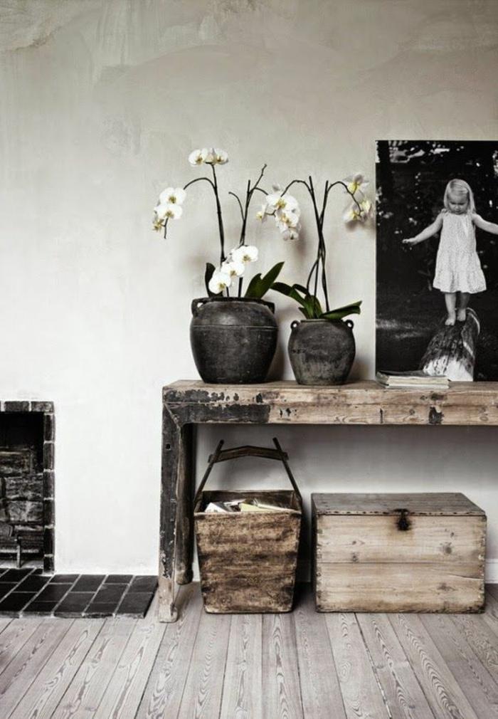 déco de console en bois, grands pots en argile, photographie noire et blanche de petite fille, caisson en bois, sol en planches rustiques