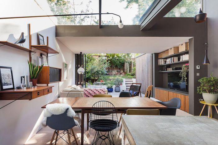 cuisine moderne qui s'ouvre sur un salon moderne abrité sous le toit d une extension avec canapé blanc, meuble tv bois et chaises