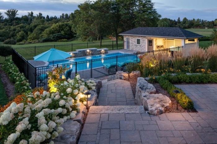 créer un jardin attirant autour de sa maison, fleurs blanches, bordures en grandes pierres blanches