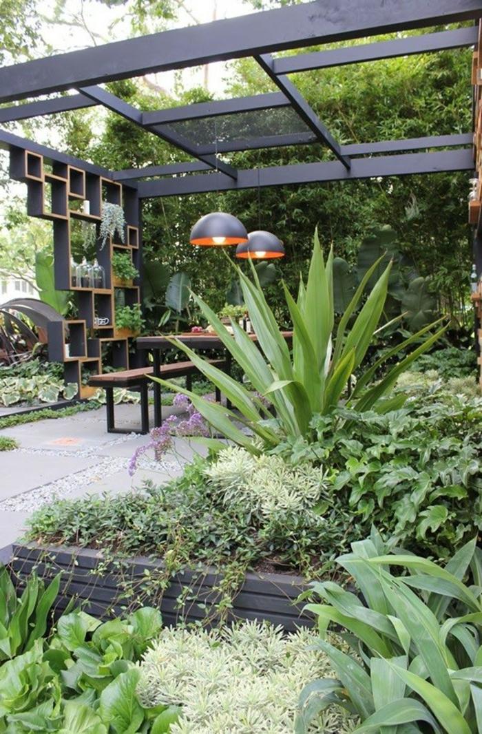 aménagement et decoration jardin paysager, tonnelle originale, grandes lampes suspendues, verdure en parterres, banquette et table