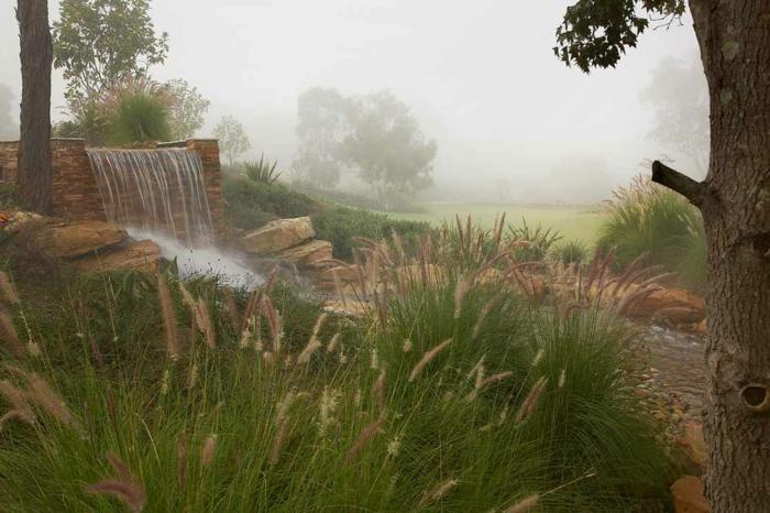 joli paysage avec plantes sauvages, cascade de jardin, grandes pierres, bois, creation jardin organique