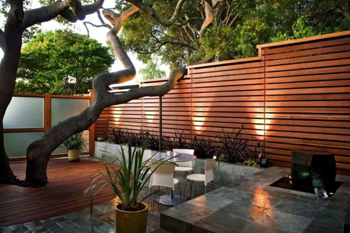 palissade en bois, arbre, dallage et terrasse en bois, table ronde avec des chaises, parterre minimaliste, cloison japonaise