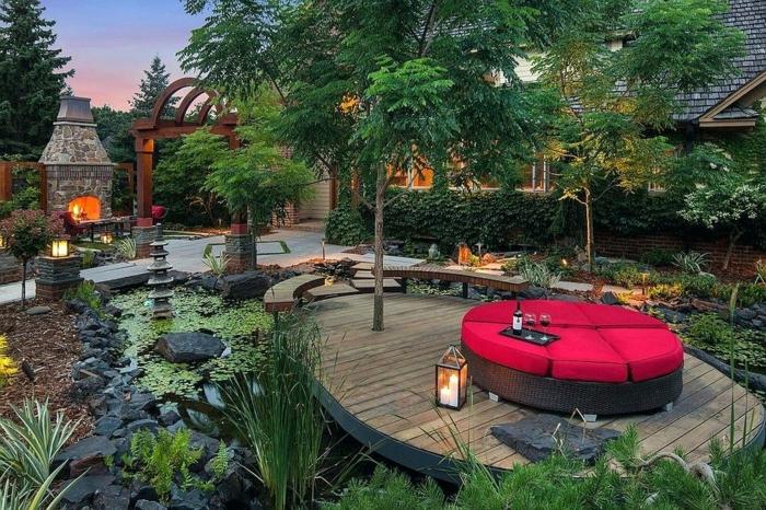 ilot de jardin au sein d'un étang, sofa rond, grand foyer, murs en briques, grandes pierres noires, lanterne