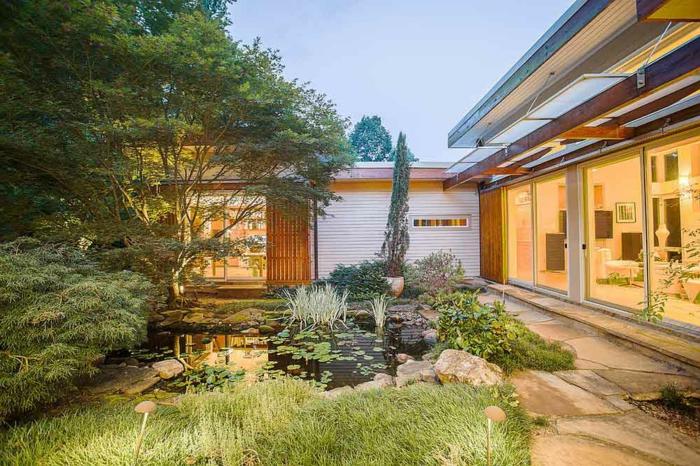 étang décoratif dans un jardin paysager, plantes aquatiques, grande maison contemporaine