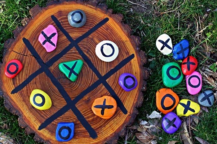 que faire pendant les vacances pour occuper les enfants, idée de jeu en plein air avec galets pions, jeu de morpions avec quadrillage sur le tronc d'arbre