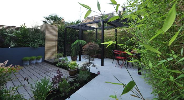 grande terrasse en béton, tonnelle noire, terrasse en bois, bambous plantés, pots de fleur, amenagement jardin paysager