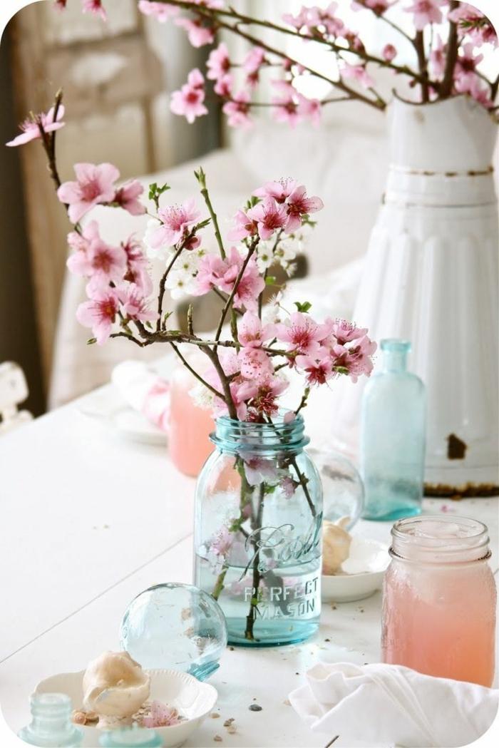 bocaux turquoises avec branches fleuries, carafe vintage blanche, bougies bricolées, idee deco table