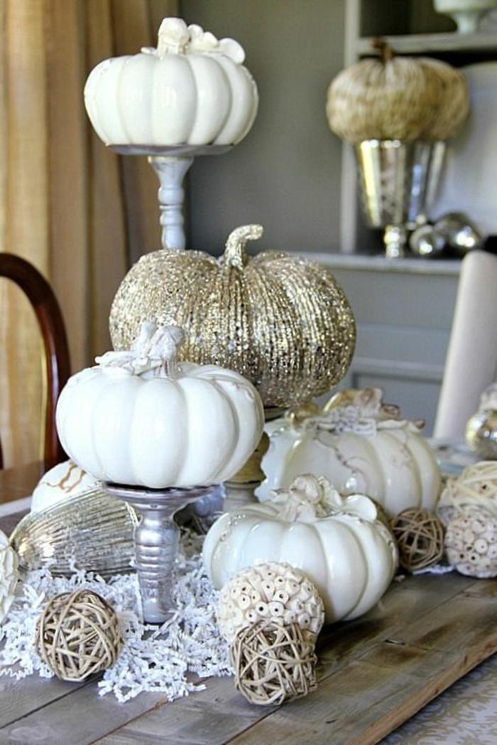 deco de table chaleureuse, citrouilles peintes blanches, objets déco, bougeoirs mis sur une table en bois