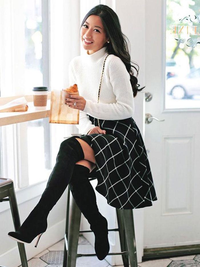 Automne-hiver 2019 tendances, cuissards et jupe, blouse à col roulé blanche, belle femme souriante avec croissant dans la main assise sur une chaise haute