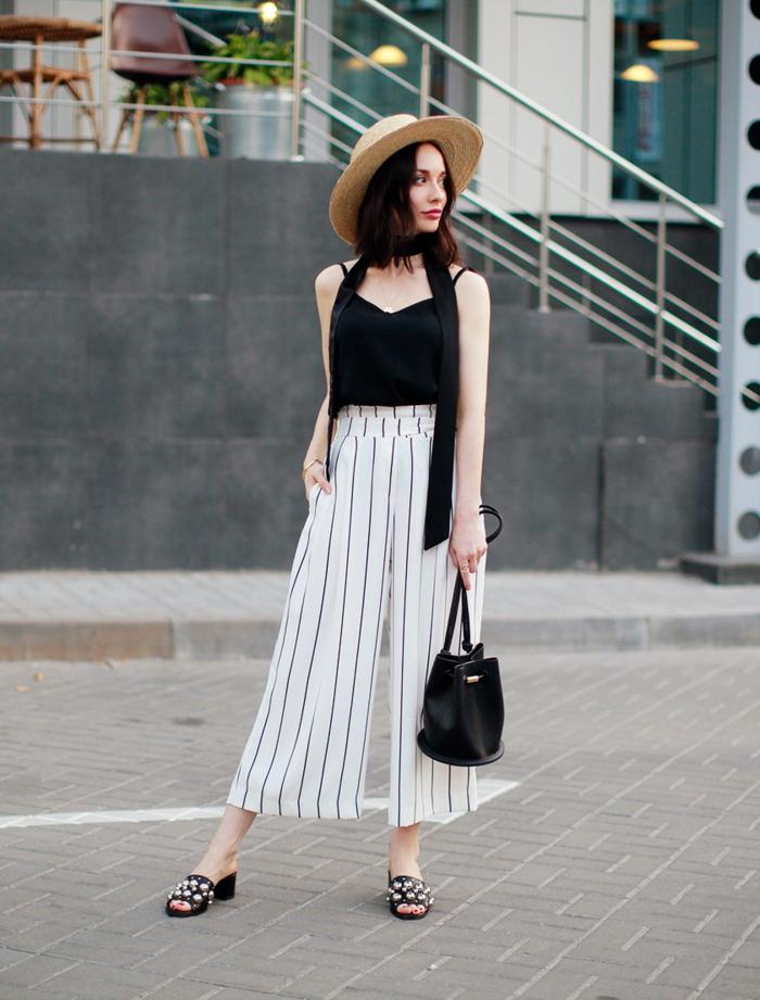 pantalon fluide rayé, sac noir cuir, top noir et sandales aux éléments métalliques incrustés; chapeau d été pour femme