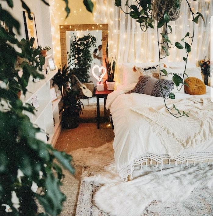 modele de chambre boheme à esprit jungle avec des plantes retombantes, et plantes en pot, linge de lit et tapis blanc, guirlandes lumineuses pour ambiance romantique