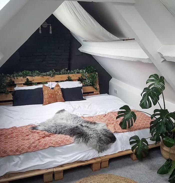 lierre d interieur et monstera deliciosa, deco chambre sous pente boheme avec lit en palette et tete de lit palette, linge de lit blanc, plaid rouge et blanc, peau animale, mur de fond noire